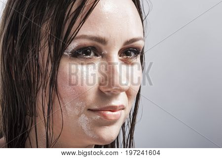 Beauty Concepts and Ideas. Portrait of Caucasian Sensual Brunette Girl Showing Wet and Shining Skin and Wet Hair. Creative Makeup. against Grey. Horizontal Image Composition