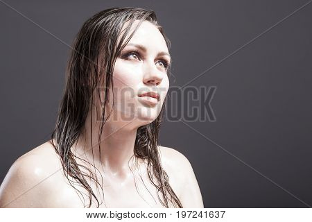 Beauty Concepts and Ideas. Portrait of Caucasian Brunette Female Looking Up with Wet and Shining Skin and Wet Hair. Against Dark Grey Background. Horizontal Shot