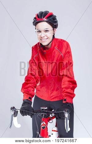 Cycling Ideas And Concepts. Portrait of Caucasian Female Cyclist Equipped in Cycling Outfit and Posing With Road Bike In Studio.Vertical Image Orientation