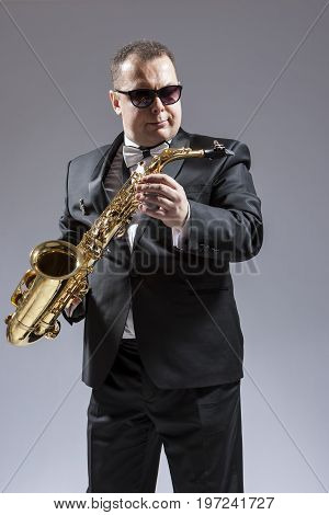 Caucasian Saxophone Player in Sunglasses Posing with Saxophone in Studio Environment. Vertical Composition