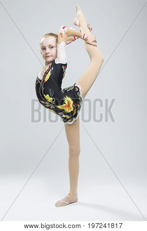 Sport concepts and Ideas. Young Caucasian Female Rhythmic Gymnast Athlete In Professional Competitive Suit Doing Vertical Split Exercise While Posing in Studio Against White. Vertical Image Composition