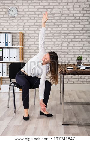 Smiling Young Female Manager Sitting On Chair Stretching Her Arms