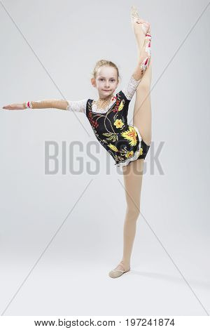 Caucasian Female Rhythmic Gymnast Athlete In Professional Competitive Suit Doing Vertical Split Exercise While Posing in Studio Against White. Vertical Image Composition