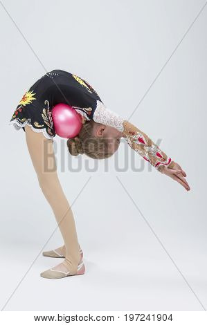 Young Caucasian Female Rhythmic Gymnast Athlete In Professional Competitive Suit Doing Backbend Stretching Exercise With Medium Ball in Studio Against White. Vertical Composition
