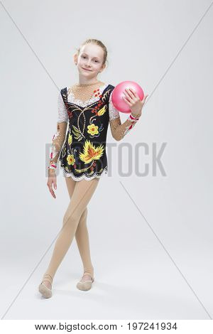 Young Caucasian Female Rhythmic Gymnast Athlete In Professional Competitive Suit Posing With Medium Ball in Studio Against White.Vertical Image Composition