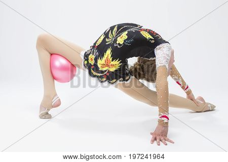 Sport Ideas. Caucasian Female Rhythmic Gymnast Athlete In Professional Competitive Suit Doing Backbend Stretching Exercise With Medium Ball in Studio Against White. Horizontal Shot