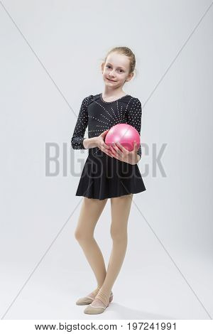 Full Length Portrait of Caucasian Female Rhythmic Gymnast In Professional Competitive Black Sparkling Suit Posing With Ball in Studio On White. Vertical Image Composition