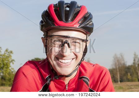 Portrait of Positive caucasian Male Road Cyclist Posing Outdoors in Helmet and Sport Outfit.Horizontal Image