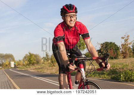 Cycling Concepts and Ideas. Smiling Caucasian Road Cyclist During Ride on Bike Outdoors. Completely Equipped in Professional Outfit.Horizontal Shot