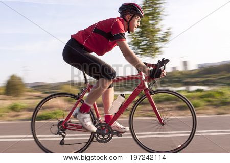 Sport and Cycling Concepts. Professional Male Cyclist in Racing Outfit During a Ride on Bike Outdoors. Panning Technique Used. Horizontal Image Composition