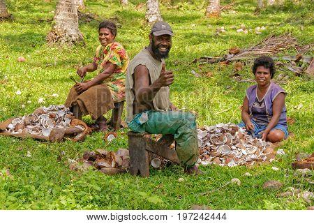A family of three smile at the camera during coconut copra harvest - Espiritu Santo Vanuatu, 26 September 2012