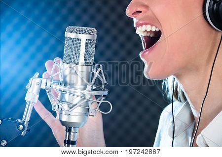 Close-up Of A Female's Open Mouth With Red Lipstick In Front Of Microphone