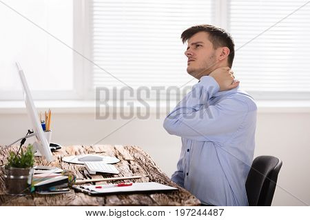 Businessman Suffering From Neck Ache Touching His Neck In Pain