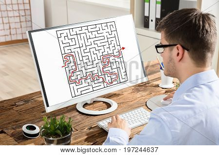 Close-up Of A Young Businessman Solving Maze On Computer At Workplace