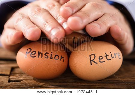 Close-up Of A Person's Hand Protecting Brown Egg Showing Pension And Retirement Text
