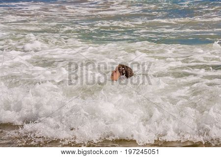 The head of a little girl stays just above the breaking ocean waves in shallow water. Her eyes are closed. The background of the water is colorful from patches of seaweed under the surface.