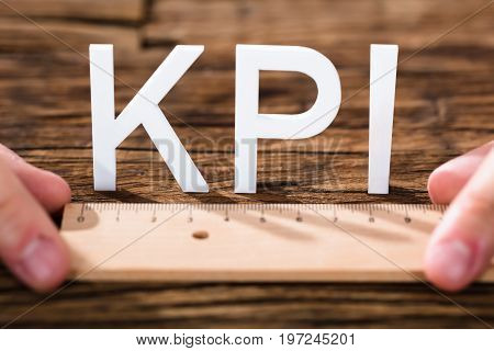 Close-up Of A Person's Hand Measuring Key Performance Indicator Over Wooden Desk