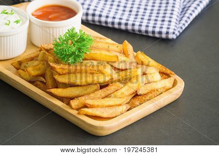 Homemade french fries serve with ketchup and sour cream or mayonnaise. Golden brown crispy french fries sprinkle with salt and oregano on plate for snack or appetizer. French fries on granite table. Delicious french fries on granite table.
