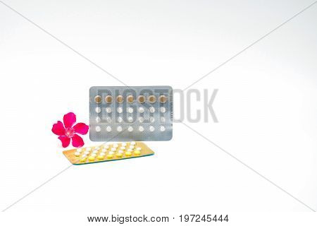 Contraceptive pills with pink flower on white background