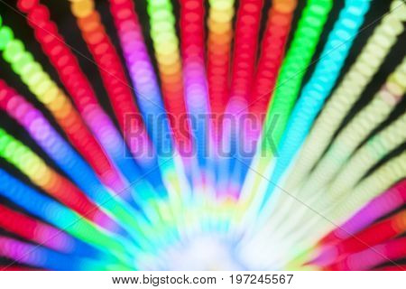 Abstract blur bokeh of colorful lights inside amusement park tunnel at night