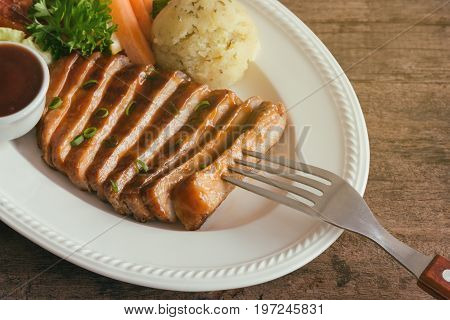 Barbecue pork steak slices on white plate. Delicious pork steak for lunch or dinner on wood table. Moist and soft homemade pork barbecue served with mash potato barbecue sauce and vegetable. Slice pork steak ready to served on wood table.