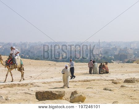 Giza, Egypt - June 30, 2008: Tourists On Camels Riding To See The Sphynx Statue And Great Pyramids W