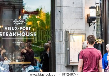 Montreal, Canada - May 27, 2017: Old Town Area With People Looking At Menu Of Steakhouse Restaurant