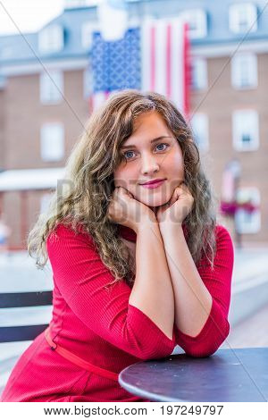 Young Woman In Red Dress Sitting Smiling With American United States Flag In Background