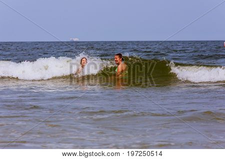 Two Sisters Swim In The Ocean On Waves