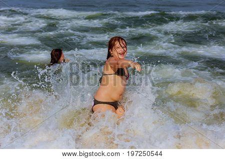 Two Little Sisters Are Swimming In Ocean.