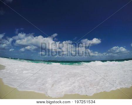 Bright tropical beach with clouds. Paradise Island, Nassau, Bahamas.