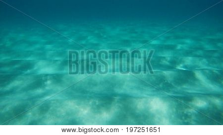 Underwater view of the sand, the light effects, and the far away darkness. Nassau, Bahamas.