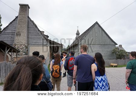 MACKINAW CITY, MICHIGAN / UNITED STATES - JUNE 18, 2017: A costumed interpreter provides a tour for visitors to Fort Michilimackinac, in the Colonial Michilimackinac State Park.