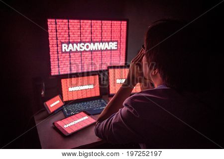 Young Asian male frustrated confused and headache by ransomware attack on desktop screen notebook and smartphone cyber attack and internet security concepts