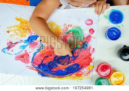Little girl painting by finger hand paint color , unlimited boundless imagination through pastel coloring posters blended on a holiday desk that does not go to school.children development concept