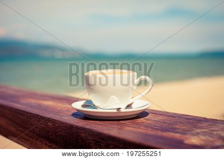 A cup of coffee in a white cup on beach abd sea background