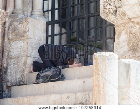 Jerusalem Israel July 14 2017 : The Pilgrim prays on the steps of the Church of the Holy Sepulchre in the old city of Jerusalem Israel.