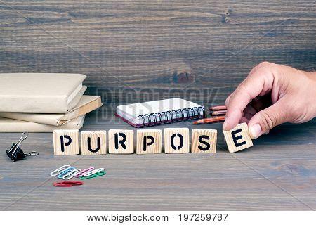 purpose concept.Wooden letters on dark background. Office desk