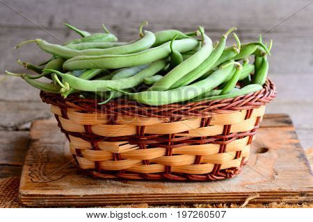 Fresh green string beans in a wicker basket and wooden board. Young green beans, natural source of dietary fiber, vitamins and minerals. Wooden background