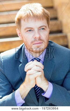 Closeup portrait of pensive young business man looking away with his hands clasped. Front view.