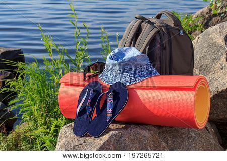 Hiking Backpack, Hat, Flip-flops, Sunglasses And Camping Mat On Rock With Sea Shore Background