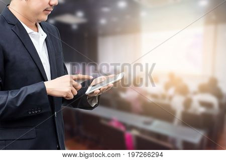 businessman using the mobile phone blurred of conference hall or seminar room with attendee background.