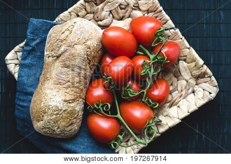 Tasty bred and tomatos on wicker plate