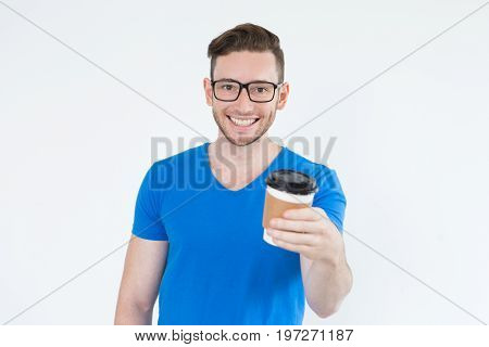 Cheerful energetic young man with take-out coffee looking at camera. Smiling smart businessman in eyeglasses offering to drink coffee. Coffee to go or student life concept