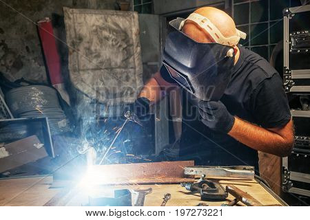 A bald man in a black T-shirt creates with his own hands a mettalical product and welds the metal with a welding machine in a dark environment in the background metal boxes many tools on the table