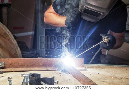 A bald strong man in black work clothes welds a metal welding machine in a dark workshop many sparks fire and smoke