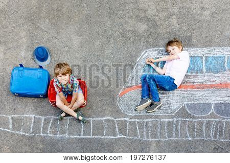 Two little kids boys having fun with train picture drawing with colorful chalks on asphalt. Children having fun with chalk and crayon painting and game going on vacations. Friends with suitcases.