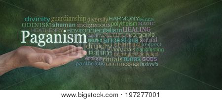 Paganism Word Cloud - Male hand outstretched on a green stone effect background with the word PAGANISM floating above surrounded by a relevant word cloud