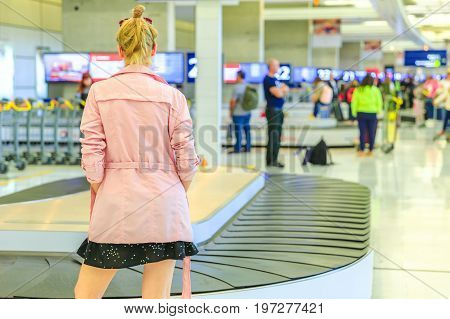Baggage reclaimed at the airport. Back of elegant caucasian woman waiting her suitcase off the carousel baggage. Business woman standing in front of conveyor belt at airport. Blurred backgorund.
