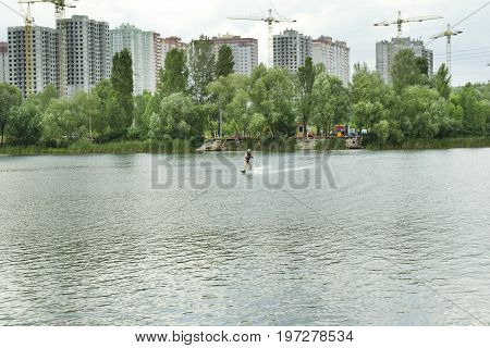 Man is wakeboarding on the lake in summer